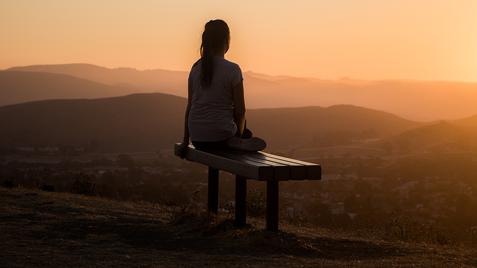 girl sitting on bench looking over mountains at sunset